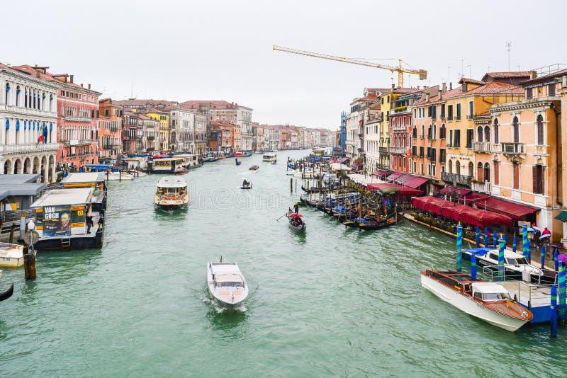 De bussen van het Vaporettoswater, gondels, watertaxis & andere boten die tussen kleurrijke Venetiaanse gebouwen op Grand Canal i stock afbeelding