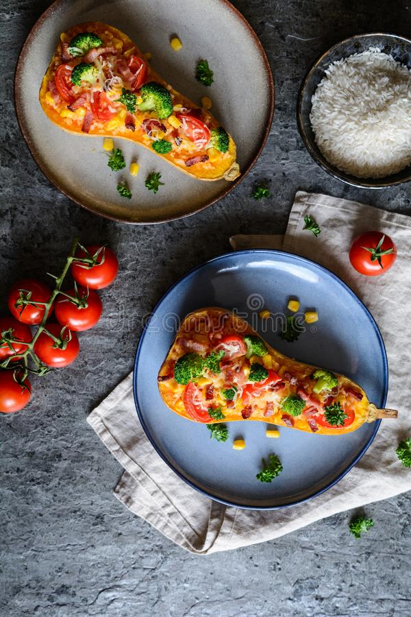 De Butternutpompoen vulde met rijst, bacon, broccoli, tomaat, graan en kaas royalty-vrije stock foto