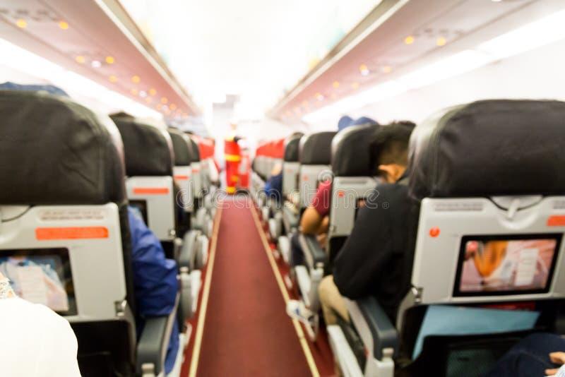 De cabinebinnenland van het Defocusedvliegtuig met zetels en passagiers stock foto