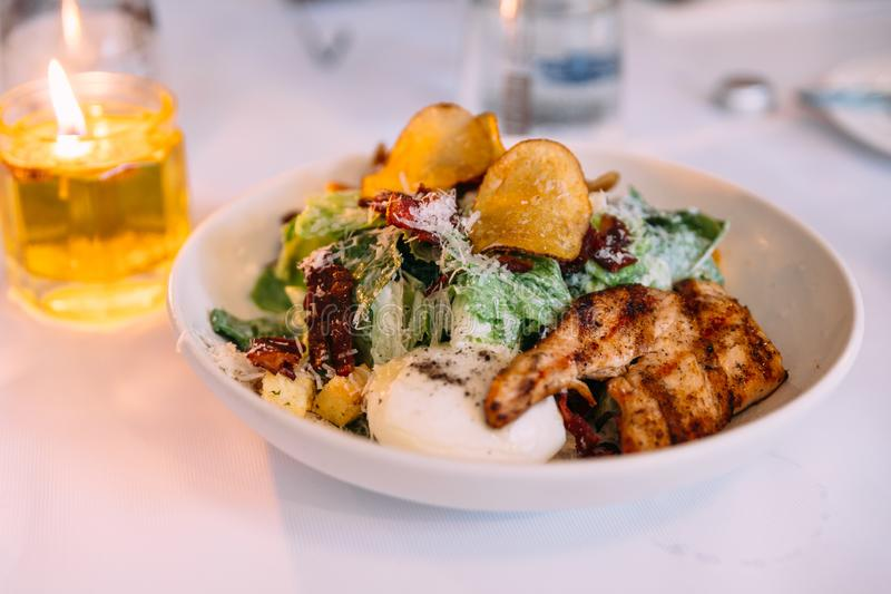 De Caesarsalade diende met gekookt ei, spaanders en roosterde kippenborst royalty-vrije stock fotografie