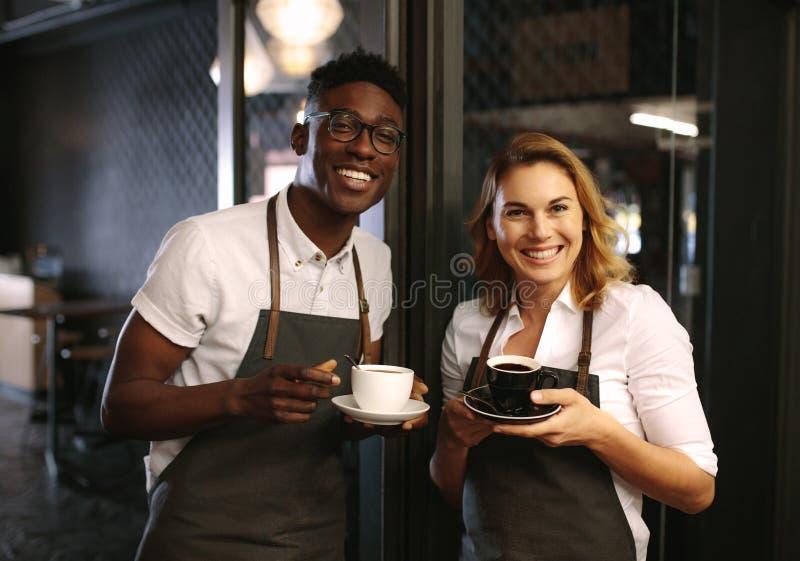 De Caféeigenaars bij hun koffie winkelen de koppen van de holdingskoffie royalty-vrije stock fotografie