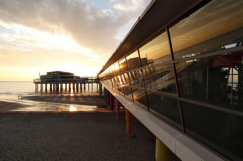 De cais na praia schevening perto do haag do antro no por do sol imagens de stock