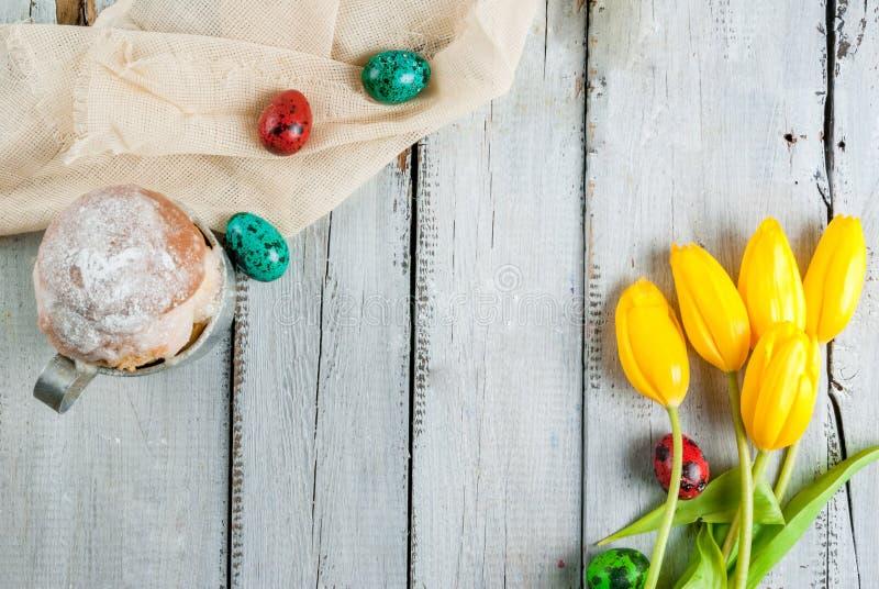 De cake en de eieren van Pasen met tulpen stock afbeeldingen