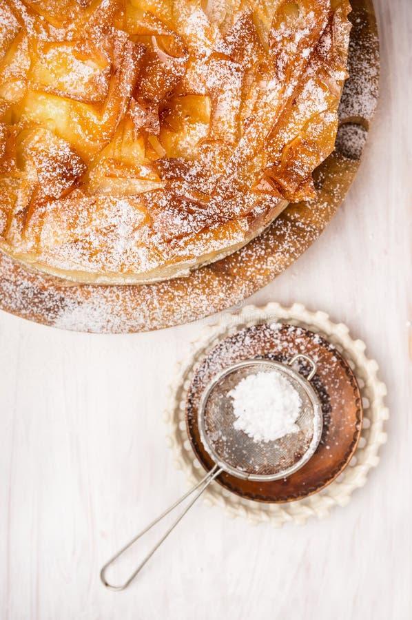 De cake en het Zeefje Spoon van het Filogebakje op witte houten achtergrond, sluiten omhoog stock fotografie