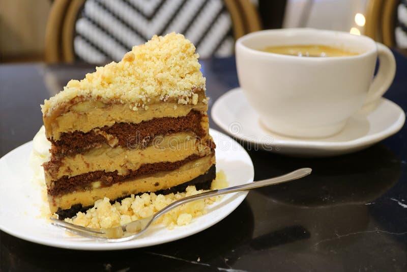De cake en de kruimeltaart van de Banoffeepastei met onscherpe kop van hete koffie op achtergrond royalty-vrije stock fotografie