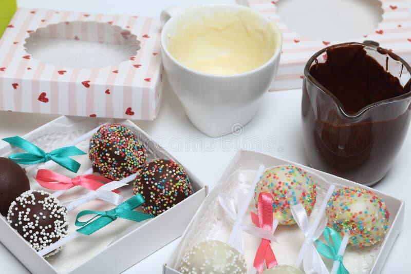 De cake knalt verfraaid met een boog van vlecht, die in een giftdoos wordt ingepakt Dichtbij zijn koppen van gesmolten chocolade stock afbeeldingen
