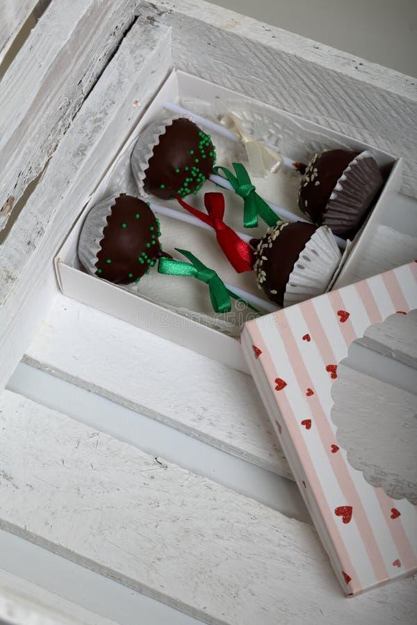 De cake knalt verfraaid met een boog van vlecht, die in een giftdoos wordt ingepakt In een houten doos geschilderd wit royalty-vrije stock afbeeldingen