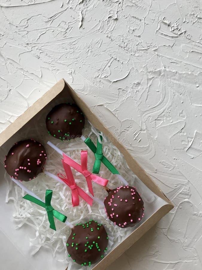 De cake knalt verfraaid met een boog van vlecht, die in een giftdoos wordt ingepakt Op de oppervlakte met decoratief pleisterwit  stock afbeelding