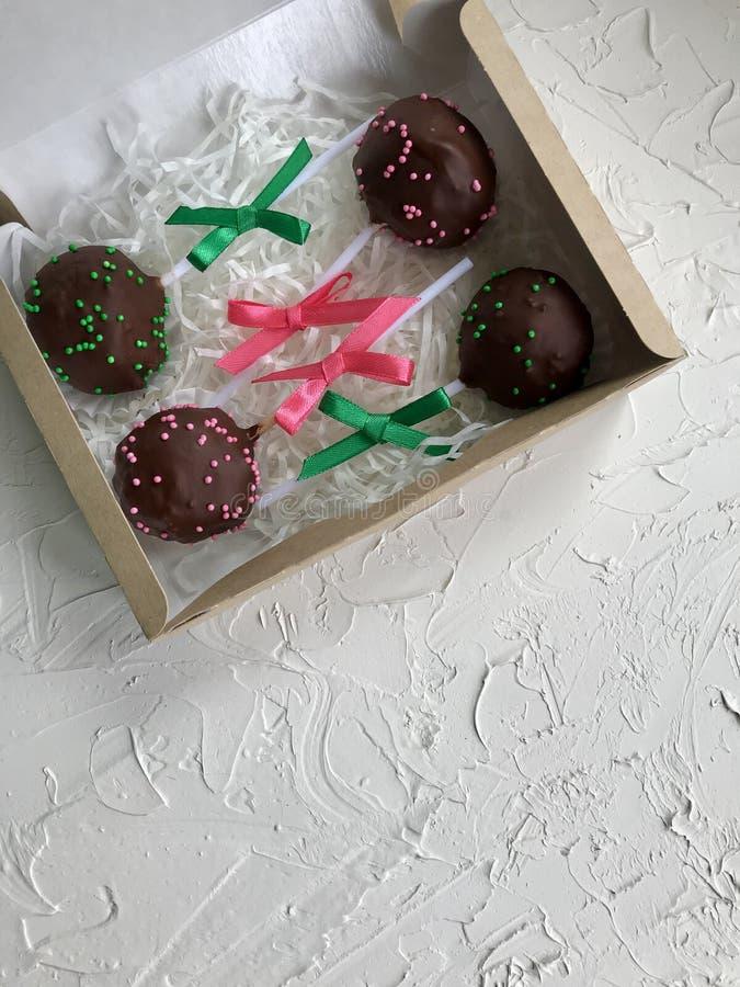 De cake knalt verfraaid met een boog van vlecht, die in een giftdoos wordt ingepakt Op de oppervlakte met decoratief pleisterwit  royalty-vrije stock afbeeldingen