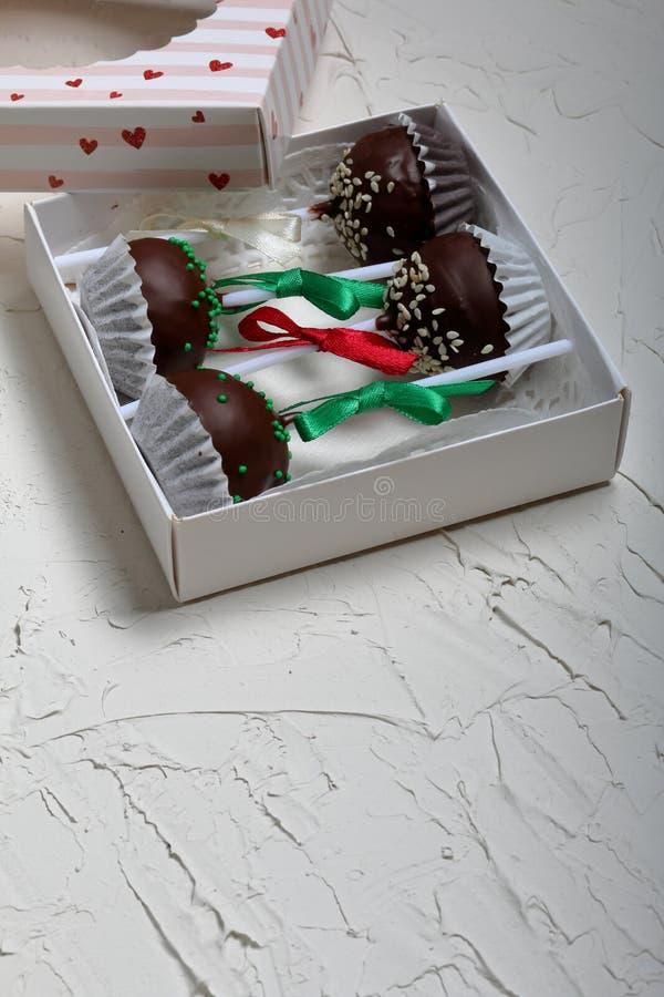 De cake knalt verfraaid met een boog van vlecht, die in een giftdoos wordt ingepakt Op de oppervlakte met decoratief pleisterwit  stock foto's