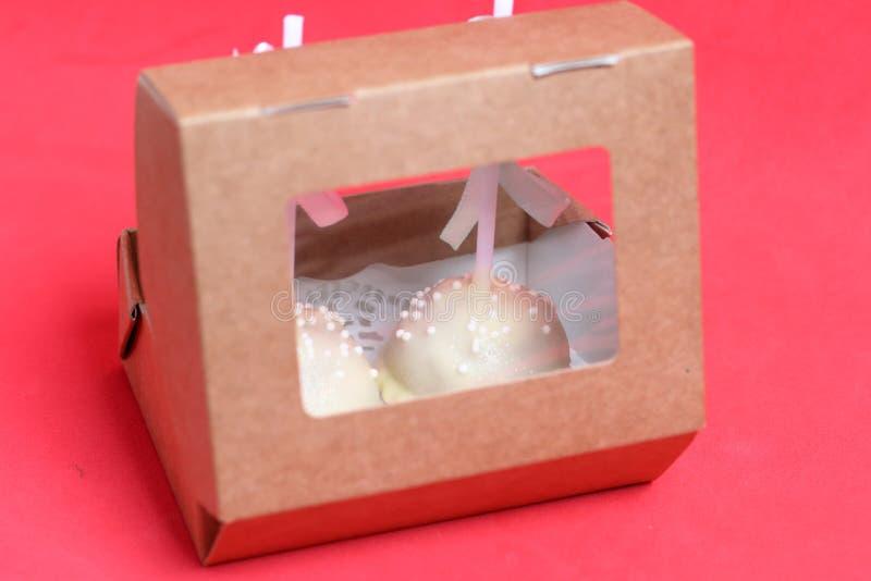De cake knalt verfraaid met een boog van vlecht, die in een giftdoos wordt ingepakt Tegen de achtergrond van koraalkleur stock foto