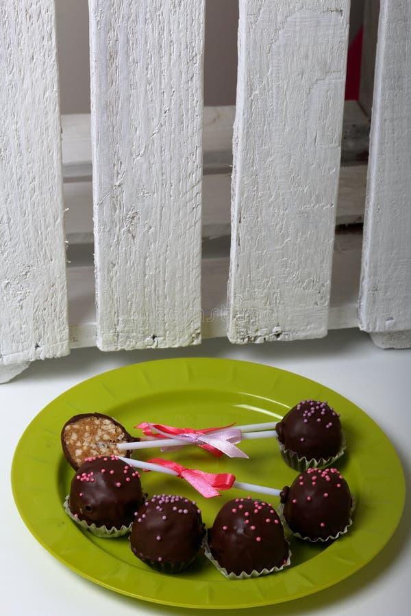 De cake knalt verfraaid met een boog van vlecht Lig op een plaat Naast de houten doos, geschilderd wit royalty-vrije stock afbeeldingen