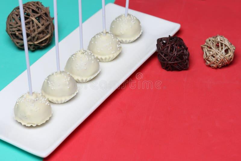 De cake knalt in witte chocoladeglans Tribune verticaal op een tribune stock afbeelding