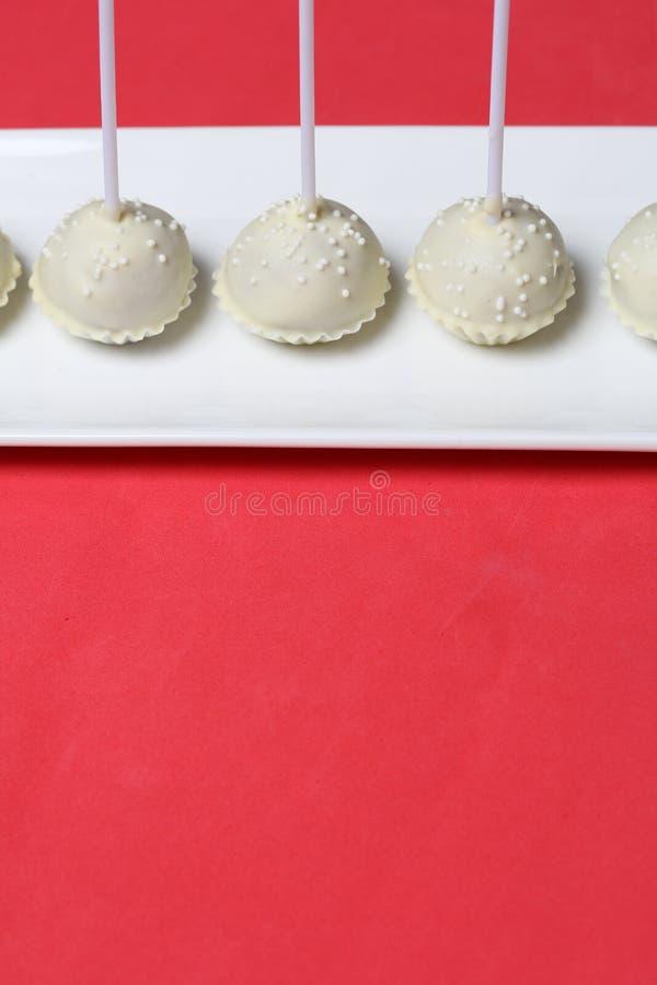 De cake knalt in witte chocoladeglans Tribune verticaal op een tribune stock afbeeldingen