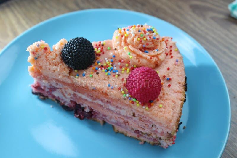 De cake met aardbeien, braambessen en kleurrijk bestrooit op de groene plaat en de kleurrijke aardbei royalty-vrije stock foto