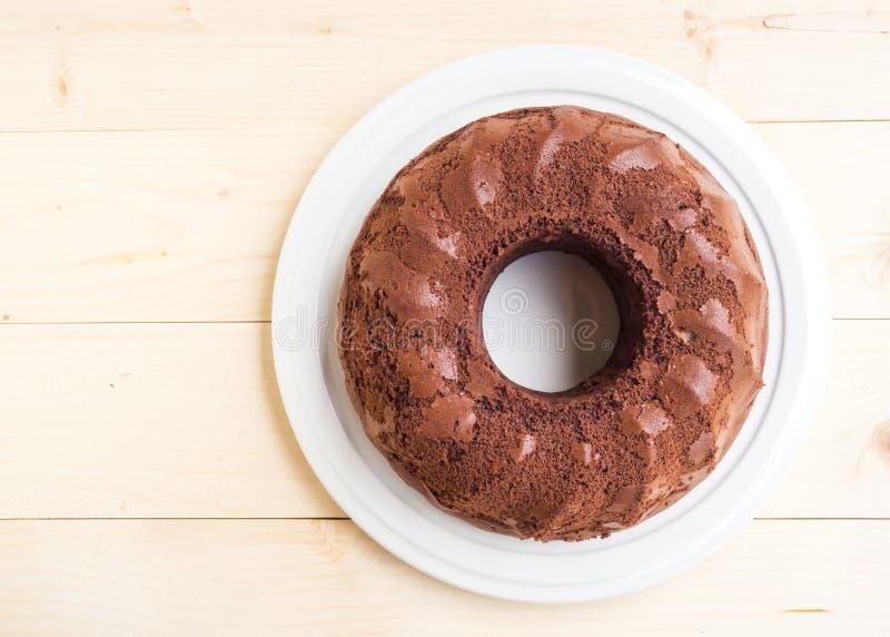 De cake van de chocolade op witte plaat Over houten lijst Hoogste mening royalty-vrije stock afbeelding
