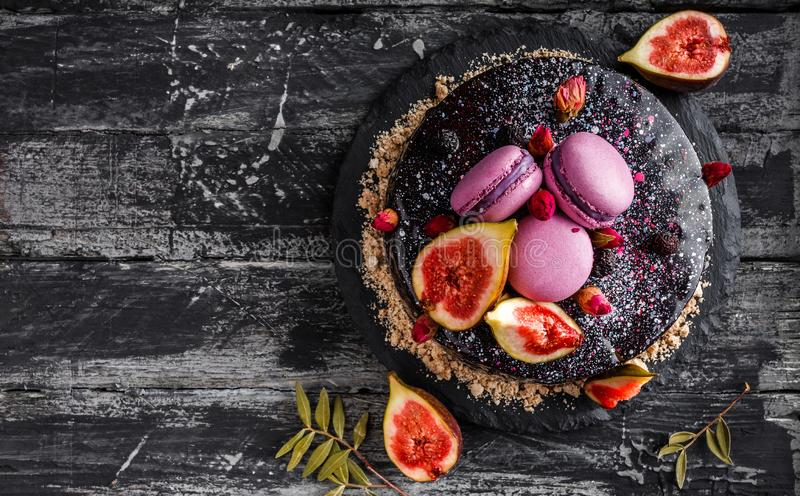 De cake van de chocolademousse met spiegelglans met makarons, fig., bloemen op donkere rustieke achtergrond wordt verfraaid die V stock fotografie