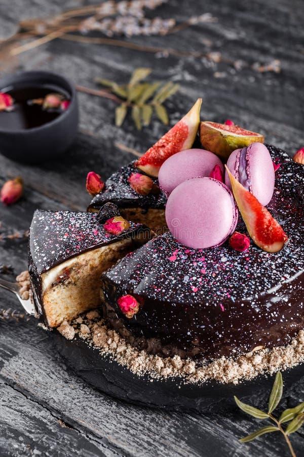 De cake van de chocolademousse met spiegelglans met makarons, fig., bloemen op donkere rustieke achtergrond wordt verfraaid die V stock foto's
