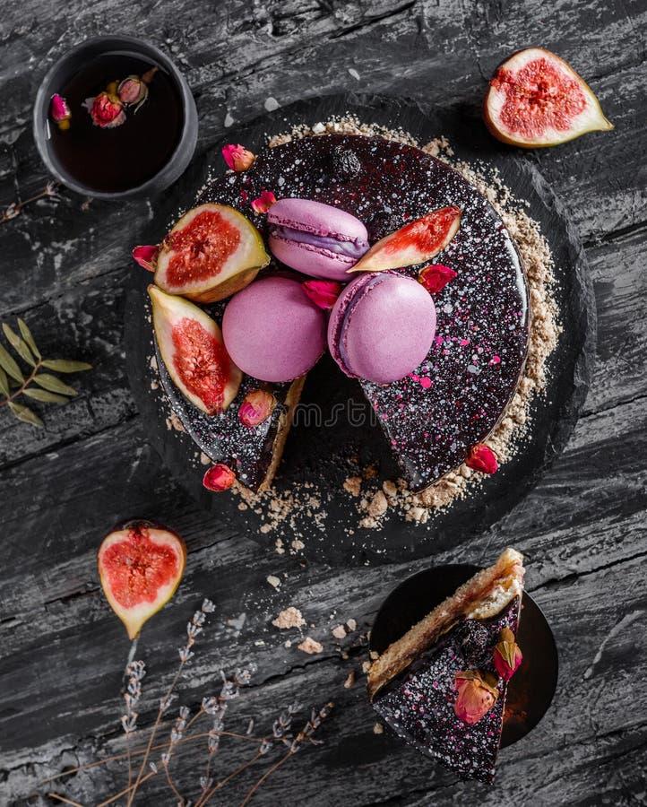 De cake van de chocolademousse met spiegelglans met makarons, fig., bloemen op donkere rustieke achtergrond wordt verfraaid die V royalty-vrije stock foto