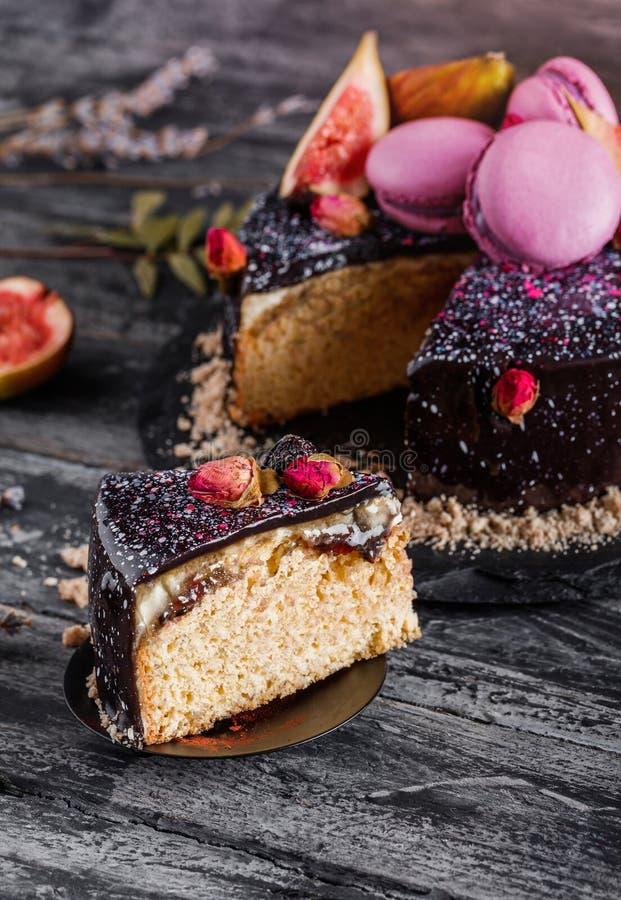 De cake van de chocolademousse met spiegelglans met makarons, fig., bloemen op donkere rustieke achtergrond wordt verfraaid die D stock fotografie