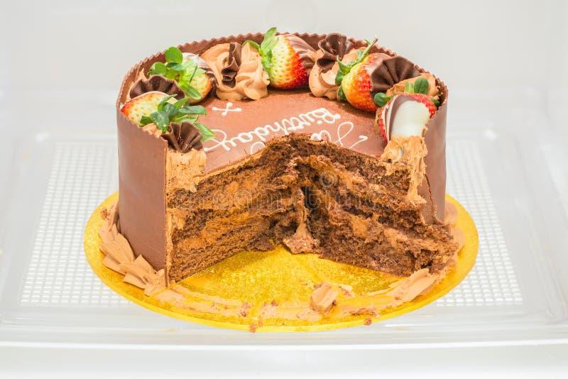 De cake van de chocoladeverjaardag, in een refigerator gedeeltelijk wordt gegeten die stock foto's
