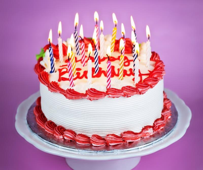 De cake van de verjaardag met aangestoken kaarsen stock fotografie