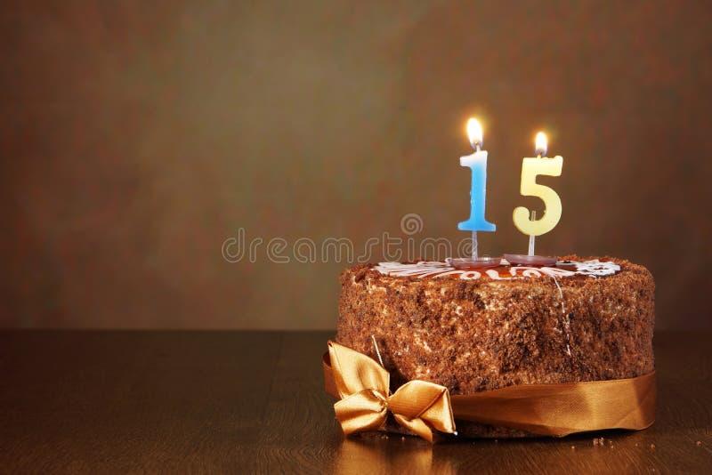 De cake van de verjaardagschocolade met het branden van kaarsen als aantal vijftien stock afbeelding