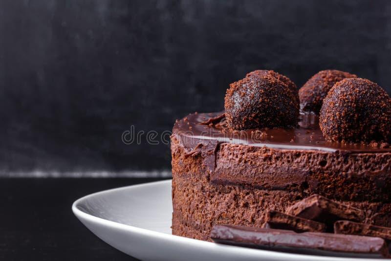 De cake van het chocoladekoekje met chocoladeglans en crumbs wordt verfraaid op een witte plaat op een donkere achtergrond die Cl royalty-vrije stock fotografie