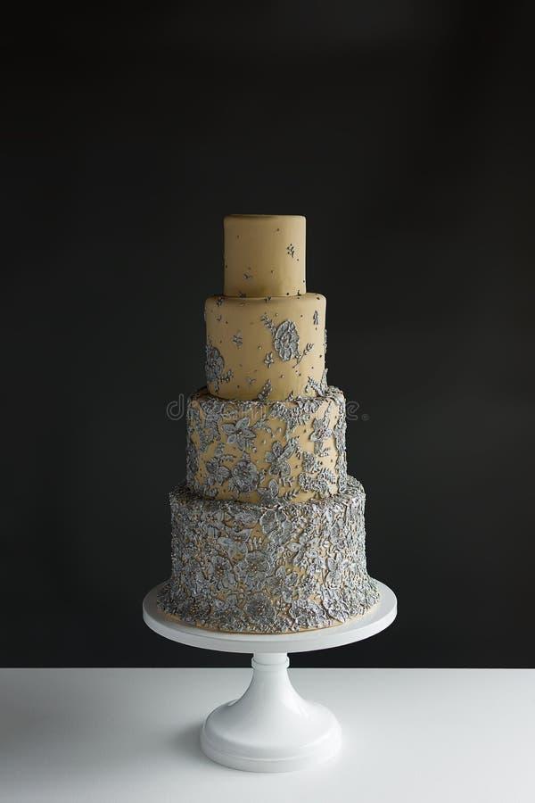de cake van het 4 rijhuwelijk met zilveren bloemenaccenten Op witte lijst met met donkere grijze ruimte als achtergrond en exempl stock fotografie