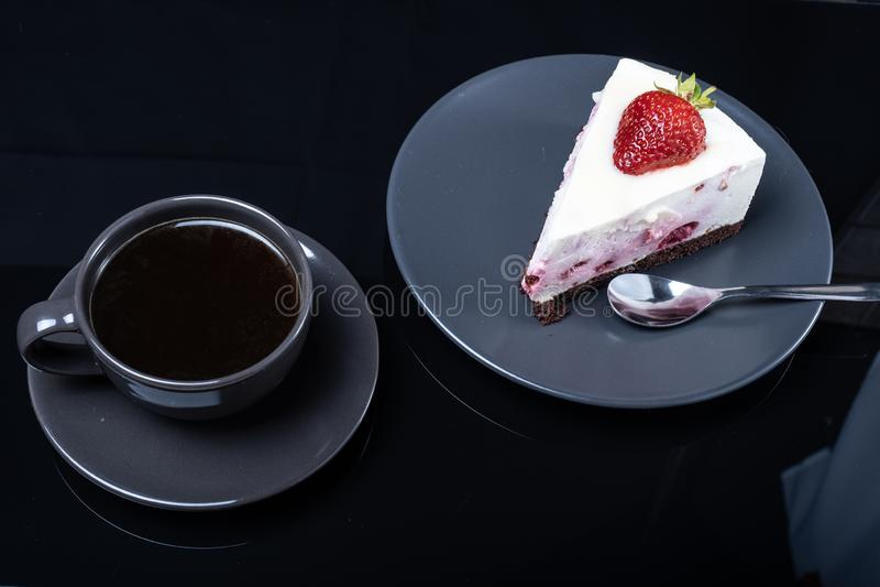 De cake van het roomfruit en een kop van zwarte koffie op een zwarte glaslijst stock fotografie