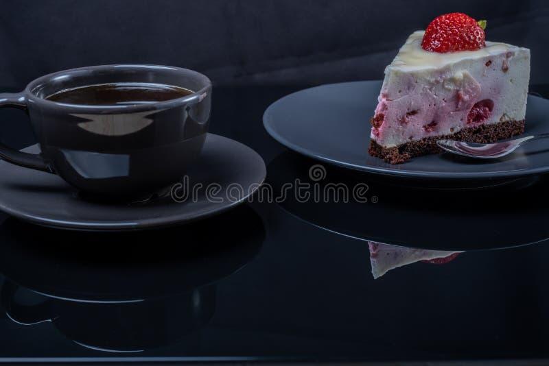 De cake van het roomfruit en een kop van zwarte koffie op een zwarte glaslijst stock foto's
