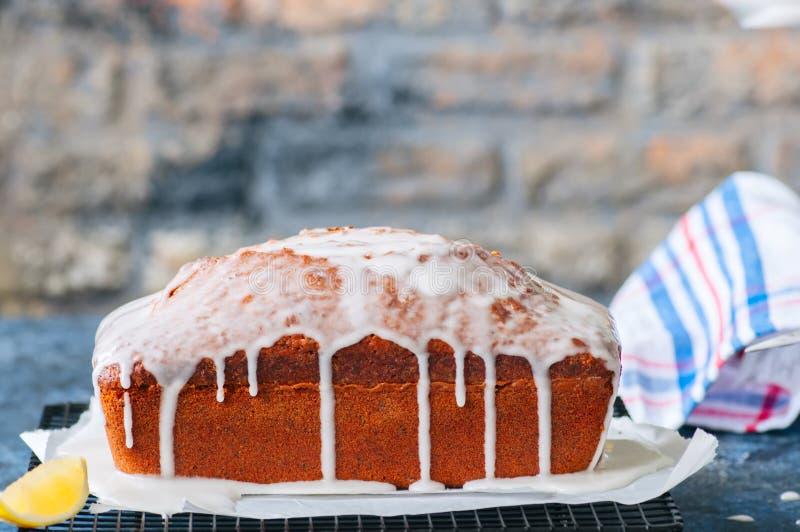 De cake van het het zaadpond van de citroenpapaver met glans op een draadrek Blauwe ston royalty-vrije stock foto