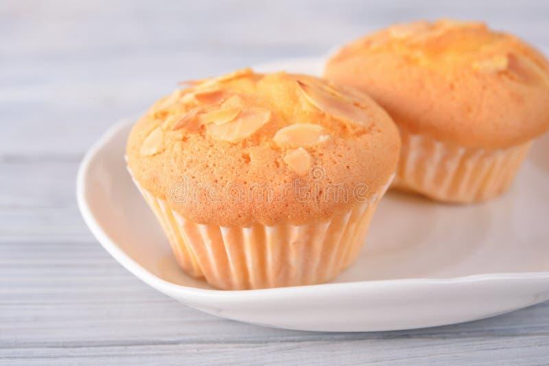 De cake van de muffinkop met amandel in witte plaat en op houten achtergrond wordt gesneden die stock afbeelding