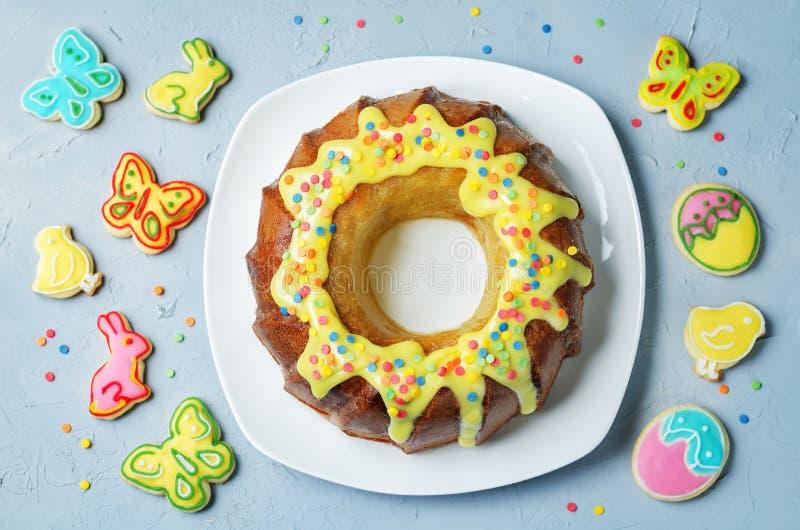 De cake van Pasen Bundt met kleurrijke bovenste laagje en Pasen-Koekjes stock foto's