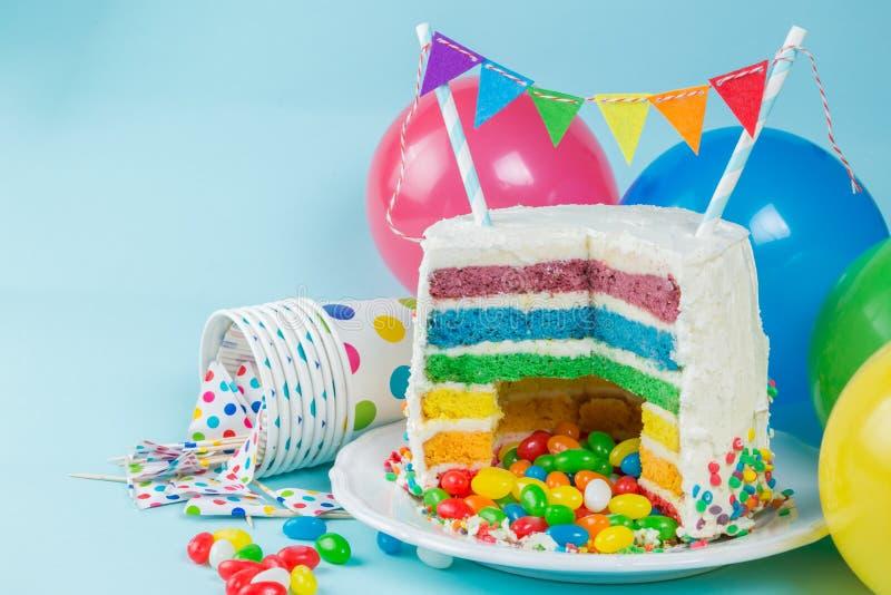 De cake van regenboogpinata met suikergoed - verjaardagsachtergrond, kaart, concept stock foto's