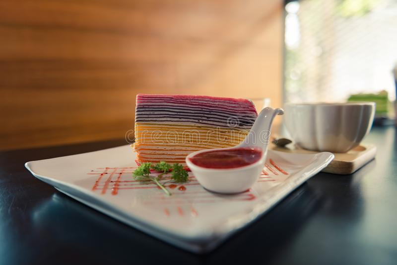 De cake van de regenboogrouwband en aardbeisaus op witte plaat met een kop van hete koffie op donkere houten lijst stock afbeeldingen