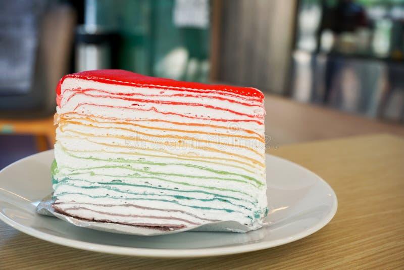 De cake van de regenboogrouwband op witte plaat op houten lijst royalty-vrije stock fotografie