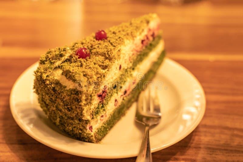 De cake van de spinazielaag met witte kaasroom, groene spinazie en verfraaid met Amerikaanse veenbessen stock foto
