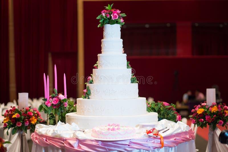De cake verfraait met roze toenam, bloem en kaars voor Huwelijksceremonie royalty-vrije stock afbeelding