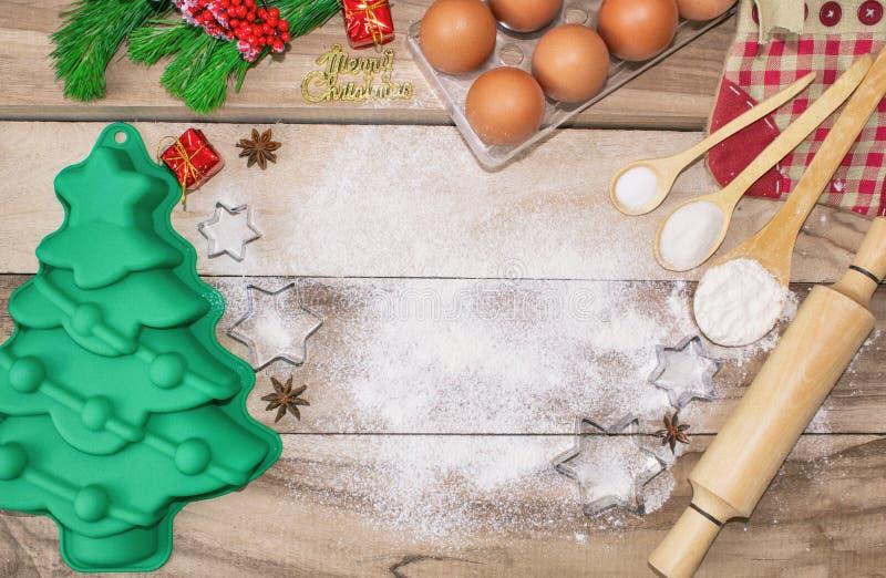De cakeachtergrond van het Kerstmisbaksel Ingrediënten en hulpmiddelen voor baksel - bloem, eieren, siliconevormen in de vorm van stock afbeeldingen