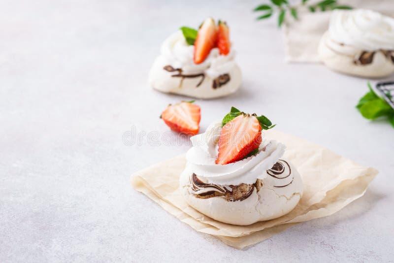 De cakes van de Pavlovabes met aardbeien, chocolade en munt stock afbeeldingen