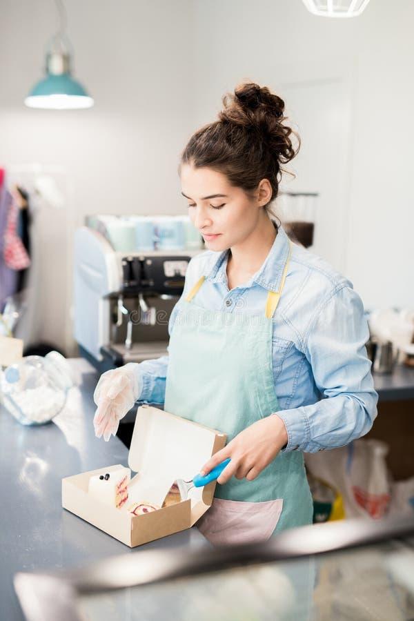 De Cakes van de vrouwenverpakking om in Koffie te gaan stock foto's
