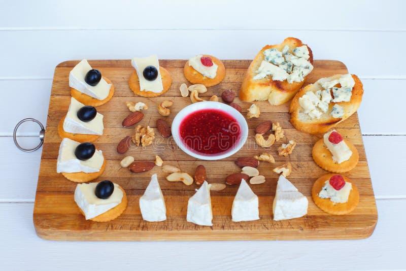 De camembertkaas, de olijven, de crackers, de noten, de jam, de Amerikaanse veenbessen en de schimmelkaasplak op broodrooster pan stock fotografie
