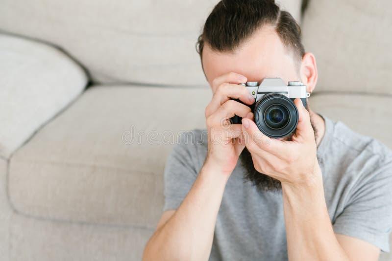 De camera die van de de mensengreep van het fotografiemateriaal lens kijken stock afbeeldingen