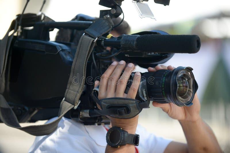 de camera van de cameramanholding tijdens gesprek op de straat royalty-vrije stock fotografie