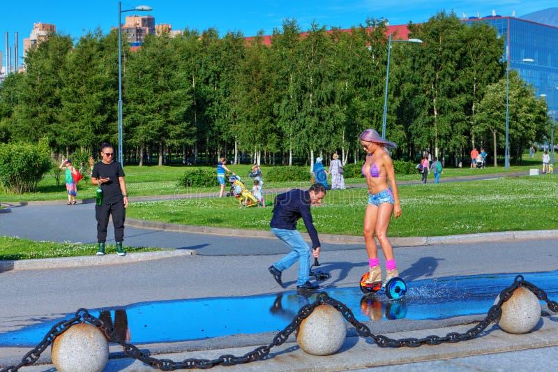De cameraman maakt een video van het meisje die op gyroscooter berijden stock afbeeldingen