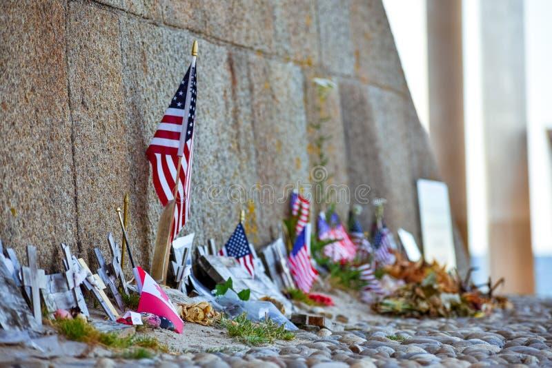 De Canadese vlaggen van Verenigde Staten en, bloemen en voorwerpen in geheugen van gevallen in het landen van Normandië stock foto