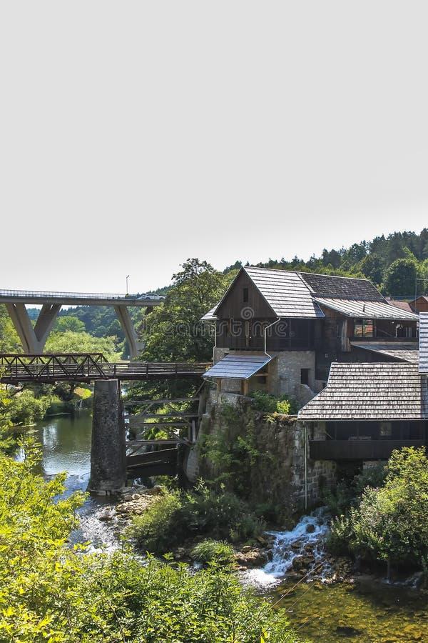 De canion en de watervallen van de Karonarivier naast een oud molenhuis in Rastoke stock afbeelding
