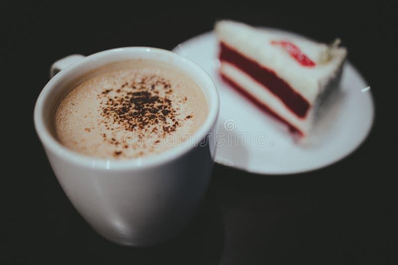 De cappuccinokoffie en de Rode Fluweelcake met Uitstekende Film zien eruit royalty-vrije stock afbeeldingen