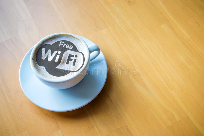 De cappuccinokop van de Wifi hete koffie met melkschuim op houten lijstachtergrond royalty-vrije stock fotografie